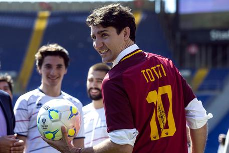Canadian Prime Minister Justin Trudeau wears a Roma soccer jersey with the number 10 of Roma's Francesco Totti at the kick off of a friendly soccer game between refugees and Fiorentina women's soccer team during the Open Goal event, a sporting event promoting social integration, at the Olympic stadium in Rome, Italy, 29 May 2017. ANSA/ANGELO CARCONI